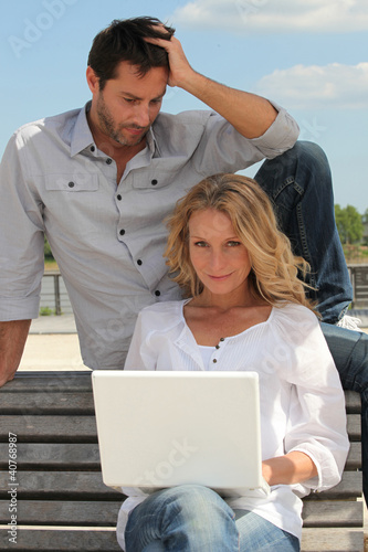 Couple with laptop outdoors