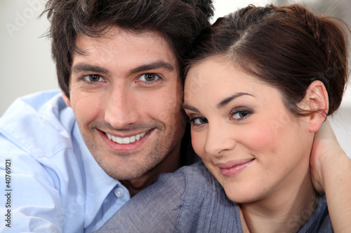 Couple sat hugging at home