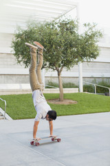 Man doing handstand on skateboard
