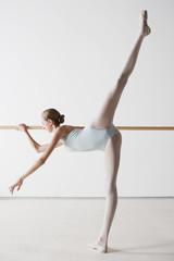 Ballet dancer stretching at barre