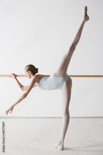 Ballet dancer stretching at barre
