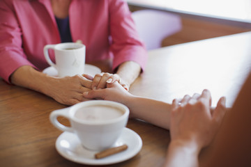 Women holding hands in cafe