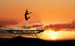 silhouette of female gymnast on trampoline in sunset