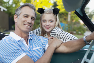 Smiling father and daughter in convertible