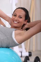 Woman doing sit-us on inflatable gym ball
