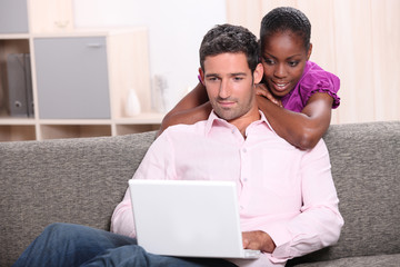 Interracial couple looking at their laptop