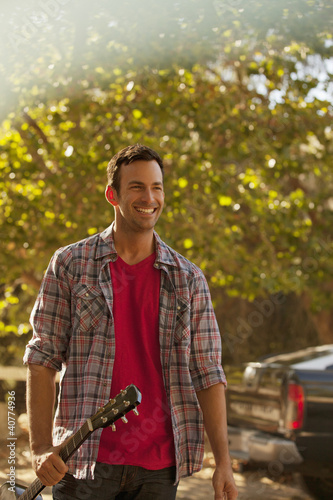 Smiling man carrying guitar outdoors