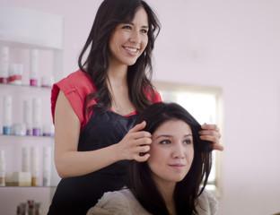 Cute hairstylist finishing customer's hair