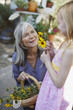 Older woman picking flowers with granddaughter