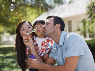 Family blowing bubbles together outdoors
