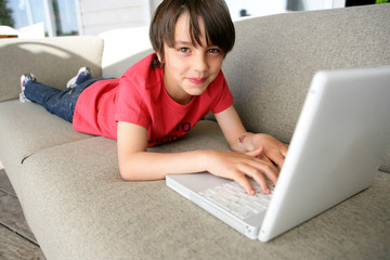 Boy using a laptop on a sofa