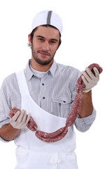 Butcher holding lots of sausages,