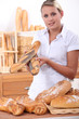 Assistant in a bakery offering poppy seeded baguettes