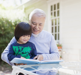Older man and grandson reading together