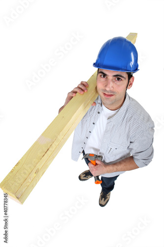 carpenter carrying planks on his shoulder with hammer
