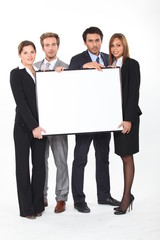 executives holding a framed board left blank for your image