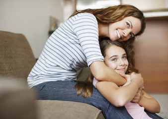 Mother and daughter hugging indoors