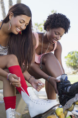Women lacing up roller skates outdoors