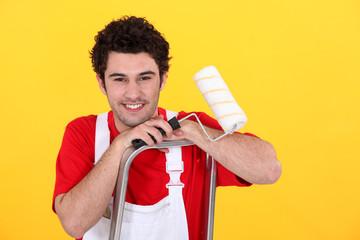 Male decorator stood in ladder