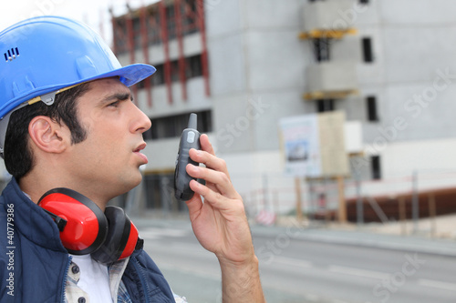 Man speaking into a walkie-talkie