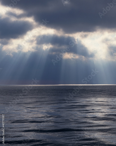 Light shining through clouds over water
