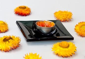 spa candle on black ceramic bowl.