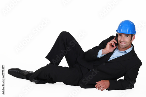 Architect laying on floor making telephone call