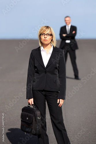 Blonde businesswoman standing far apart from her colleague