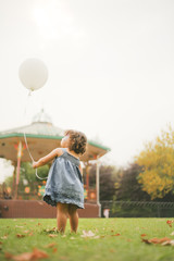 Toddler playing with balloon in park