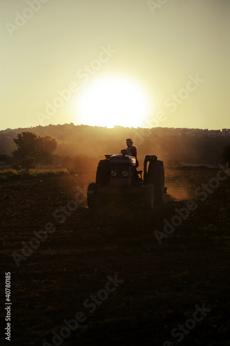 Farmer driving tractor in crop fields