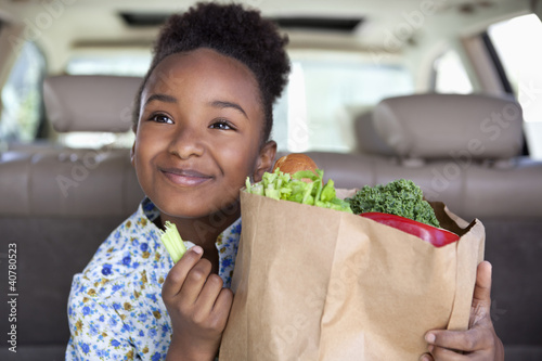 Girl eating vegetables from grocery bag