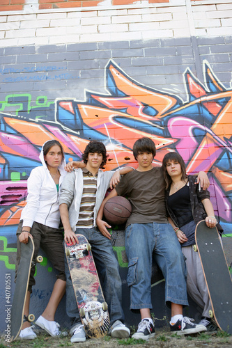 teenagers posing in front of tagged wall