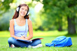 Student listening music in park