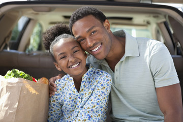Father and daughter unloading groceries from car