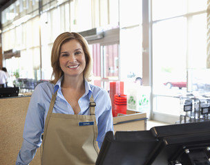 Cashier standing at till in supermarket