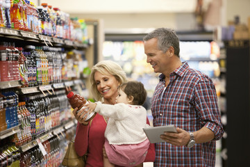Family shopping for juice in supermarket