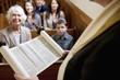 Rabbi reading from Torah scrolls in synagogue