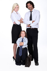 Couple in smart suit and little boy dressed as a businessman