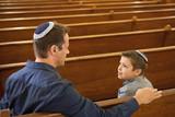 Father and son wearing yarmulkes in synagogue