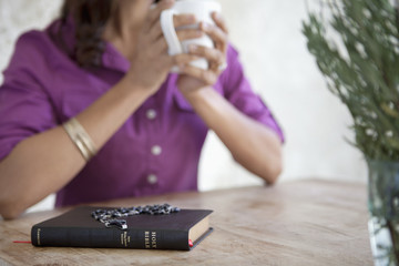 Prayer beads on Bible at breakfast table