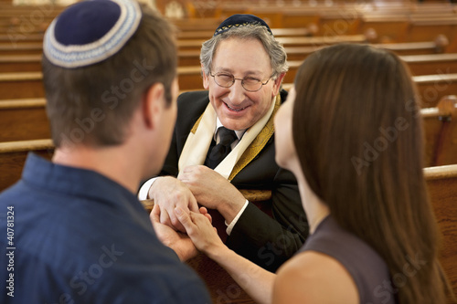 Couple talking with rabbi in synagogue