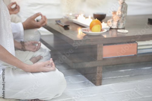 Couple meditating together in living room