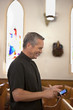 Priest using cell phone in church