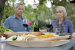 Older couple praying at dinner table