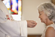 Older woman taking communion from priest
