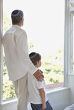 Father and son in yarmulkes standing at window