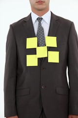 Businessman covered in yellow memo pads