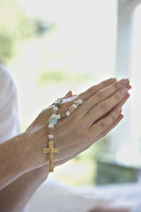 Close up of clasped hands holding prayer beads
