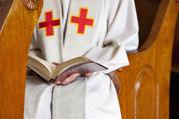 Close up of priest reading Bible