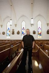 Priest standing in church pews